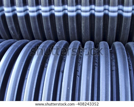 Ribbed black drain pipe surface close up texture. Pipes used for drainage and sewage systems.