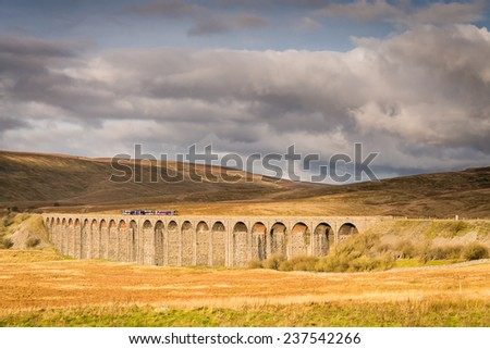 Ribblehead Viaduct with Train / The Ribblehead Viaduct carries the Settle to Carlisle Railway across Batty Moss spanning 400 m and 32 m above the valley floor - stock photo