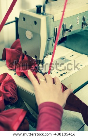 Ribbon and red cloth sewn and ruffled through a machine with tailor's hand as guide - stock photo