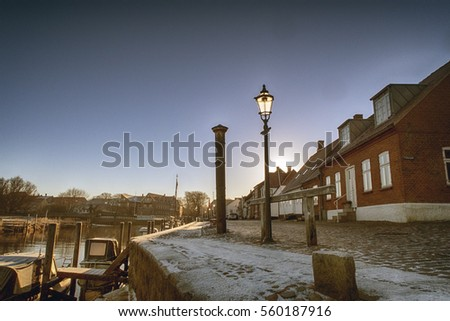 Ribe harbour and river. Winter view with vintage lamp and storm surge column. Denmark.