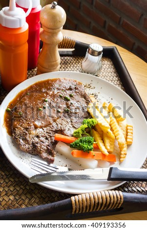 Ribeye steak on white plate. On serve tray with 