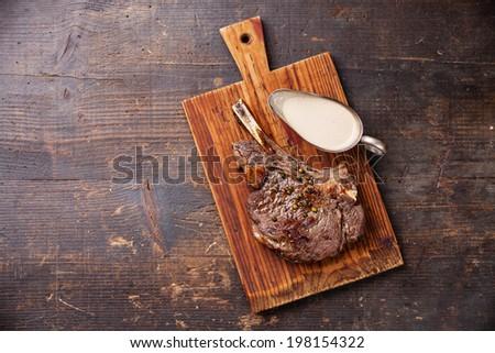 Ribeye Steak with pepper sauce on dark wooden background - stock photo