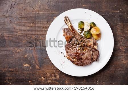Ribeye Steak with vegetables on dark wooden background - stock photo