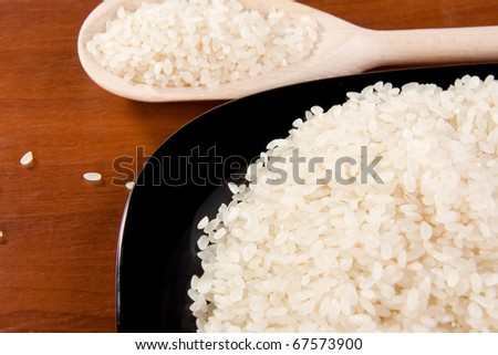 rice and ceramic black plate with spoon on table