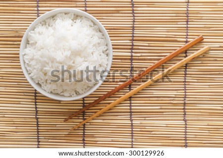 Rice bowl on bamboo mat with chopsticks - stock photo