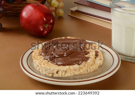 Rice cakes with hazelnut cocoa spread and a glass of milk - stock photo
