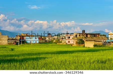 Rice fields, colourful houses and the mountains in the background, Pokhara, Nepal - stock photo
