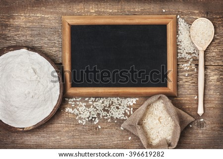 rice flour in a wooden bowl, rice on the old wooden background with copy space (Top view ) gluten-free - stock photo