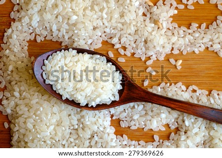 Rice grain in dark wooden spoon on wooden board - stock photo