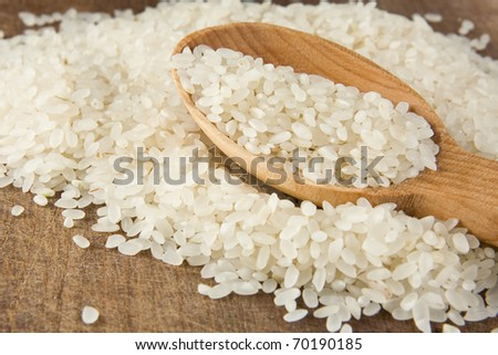 rice grain in wooden spoon - stock photo