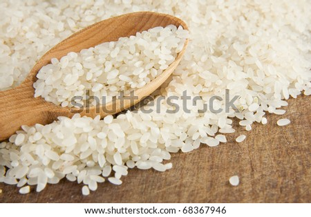 rice grain in wooden spoon on table - stock photo