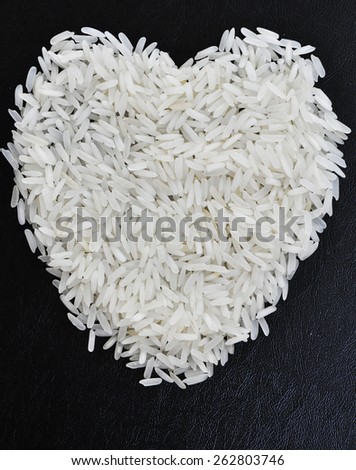 rice grains in the form of heart on a black background - stock photo