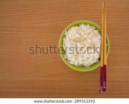 rice in a bowl and wooden chopsticks - isolated on wooden background. - stock photo