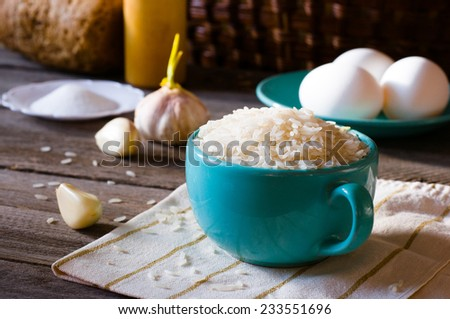 rice in a bowl, eggs and garlic on a kitchen table - stock photo