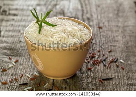 rice in a bowl on wooden table - stock photo
