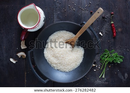 rice in a frying pan with parsley , pepper and water on the  dark background - stock photo