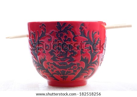 Rice in red ceramic bowl with sticks - stock photo