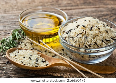 Rice in wooden spoon on kitchen table  - stock photo