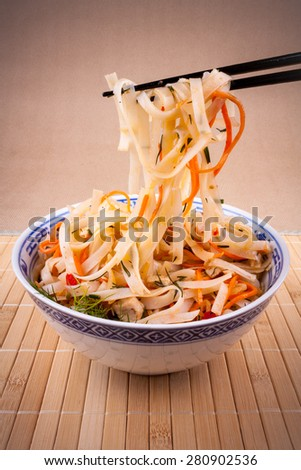 Rice noodle and carrot with chopsticks taken, close up
