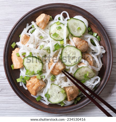 rice noodles with chicken and cucumbers close-up on a plate. horizontal view from above  - stock photo