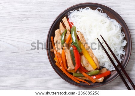 Rice noodles with chicken and vegetables close-up on the table. horizontal view from above  - stock photo