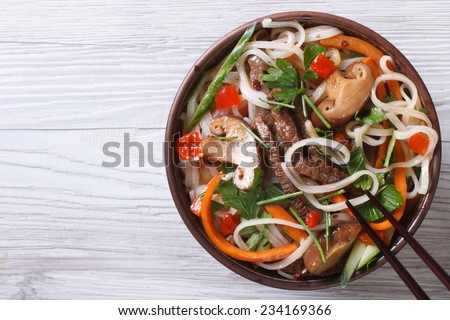 rice noodles with meat, vegetables and shiitake mushrooms closeup. top view of a horizontal  - stock photo