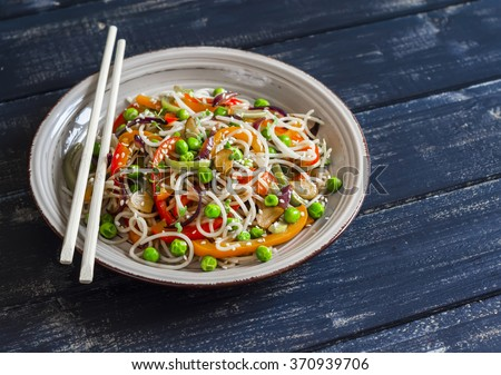 Rice noodles with vegetable stir fry on the ceramic plate on dark wooden background - stock photo