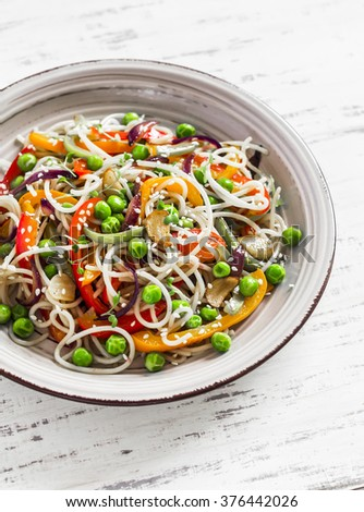 Rice noodles with vegetable stir fry on the ceramic plate on  wooden background - stock photo