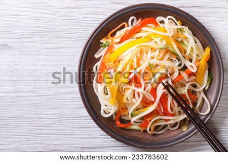 Rice noodles with vegetables close-up on a plate with chopsticks. horizontal view from above  - stock photo