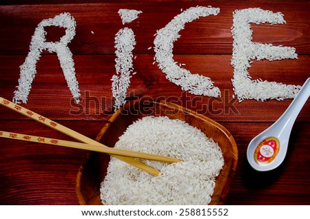 Rice on wooden table with chopsticks