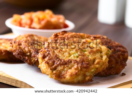 Rice patties or fritters made of cooked rice, carrot, onion, garlic, celery stalks, tomato sauce in the back, photographed with natural light (Selective Focus, Focus on the middle of the first patty) - stock photo