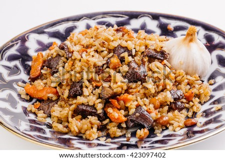 Rice pilaf with lamb meat and vegetables. Cooked with fried lamb, rice, garlic, carrot and raisins.