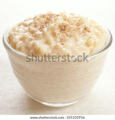 Rice pudding sprinkled with nutmeg in an individual glass bowl. - stock photo
