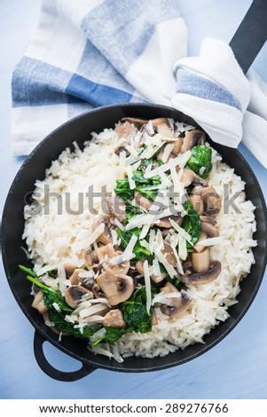 Rice (risotto) with mushrooms, parmesan and spinach top view on blue wooden background. Italian cuisine. - stock photo