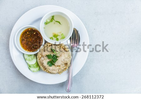 Rice roast chicken with spoon and fork on white plate. - stock photo