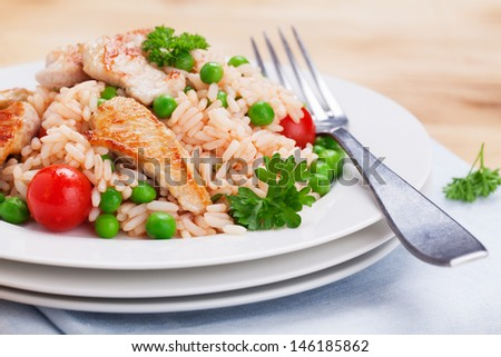 Rice salad with turkey breast, tomatoes, peas and parsley on a brown wooden plate - stock photo