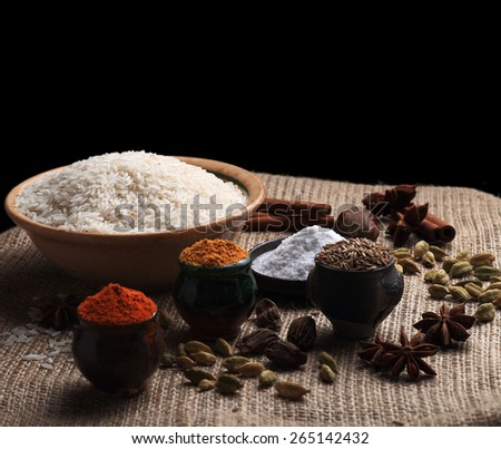 Rice, spice powders and seeds on the table covered with burlap cloth. Black background - stock photo