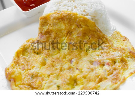 Rice, topped with omelet, dip chili sauce - stock photo