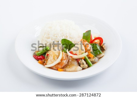 Rice topped with stir-fried seafood and basil - stock photo