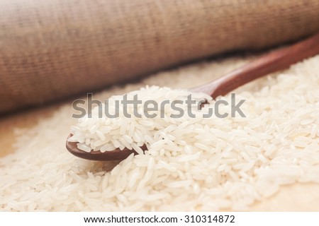 Rice, White rice in wooden spoon with hemp sack background, Selective focus