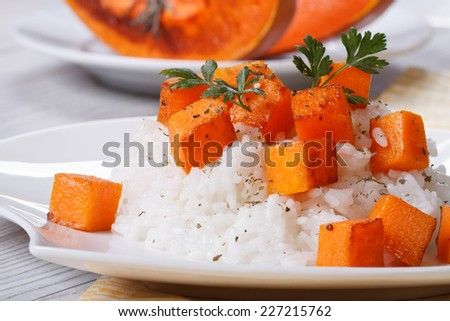 Rice with baked pumpkin close-up on a plate. horizontal