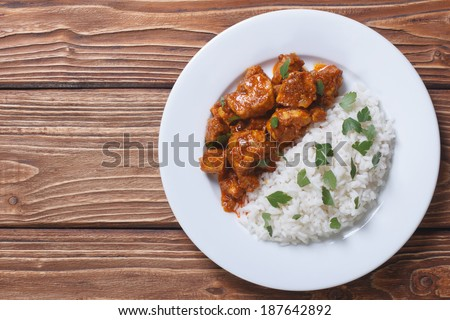 Rice with chicken in curry sauce and herbs on a plate with a horizontal top view.  - stock photo
