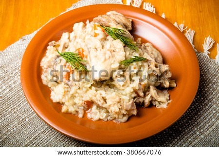 Rice with chicken on a clay plate on linen napkin. Toned.