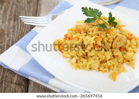 Rice with chicken on a white plate on the wooden table - stock photo