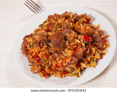 Rice with meat and vegetables on plate