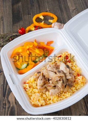 Rice with meat, vegetables, mushrooms and salad in lunch box - stock photo