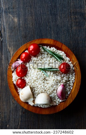 Rice with raw vegetable for cooking in bowl on dark rustic wood texture, top view - stock photo