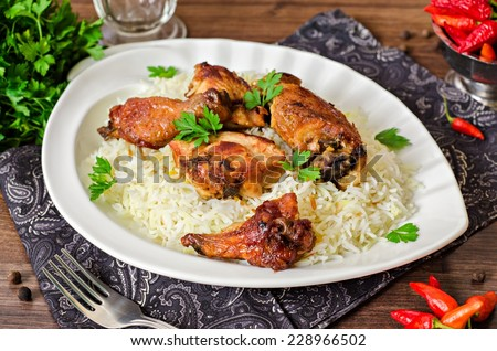 Rice with roasted chicken wings in white plate - stock photo