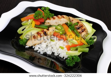 Rice with slices of chicken breast and vegetables - stock photo