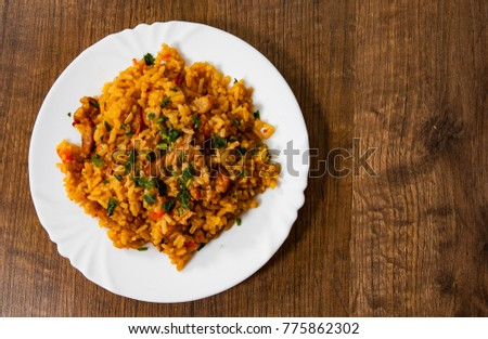 Rice with Vegetables and Meat in a plate on wooden table. with copy space. top view